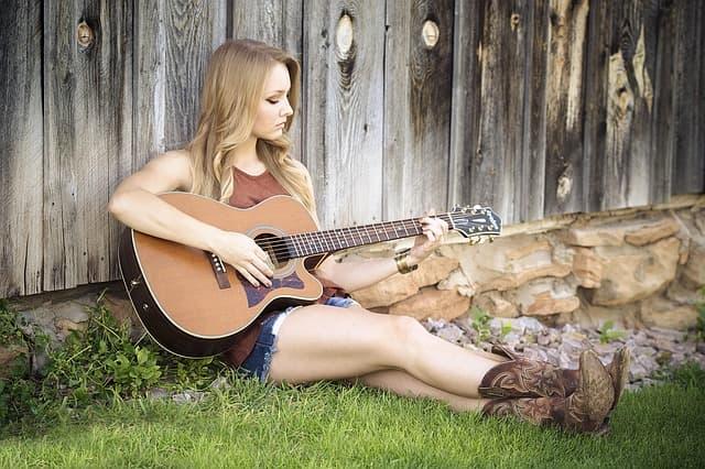 ギターで音楽を奏でる女性の画像