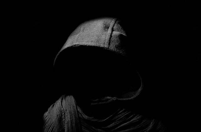 暗闇の中にフード姿の人影