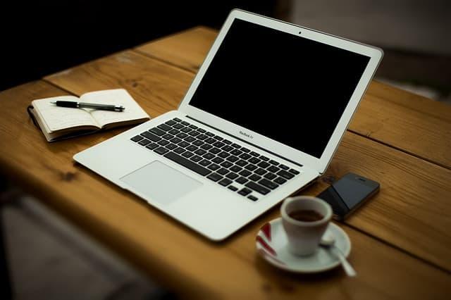 コーヒーを飲みながら仕事をしている画像