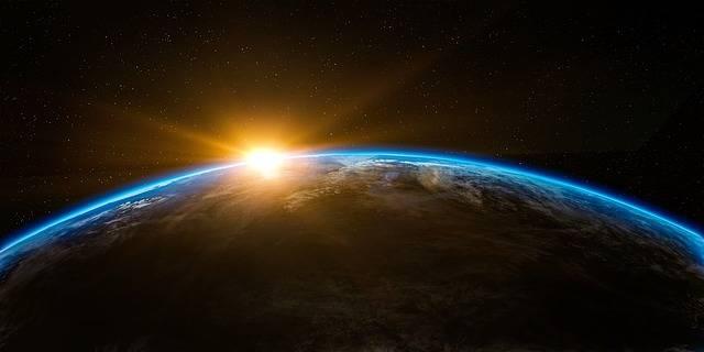 宇宙から見た地球と日の出のイメージ画像